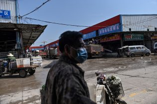 """This photo taken on April 15, 2020 shows a man wearing a face mask while walking at the Wuhan Baishazhou Market in Wuhan in China's central Hubei province. - China's """"wet"""" markets have gained a bad international reputation as the coronavirus roiling the world is believed to have been born in stalls selling live game in Wuhan late last year. (Photo by Hector RETAMAL / AFP) / TO GO WITH Health-virus-China,SCENE by Jing Xuan Teng (Photo by HECTOR RETAMAL/AFP via Getty Images)"""