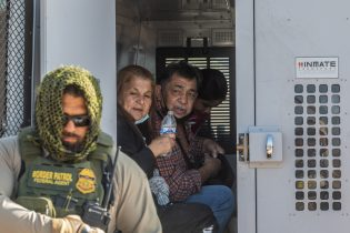 YUMA, AZ - MAY 13: A family of asylum seekers from Colombia boards the Border Patrol Inmate transport after they turned themselves in to US Border Patrol agents on May 13, 2021 in Yuma, Arizona. The Biden administration is trying to develop a plan to safely handle the surge of immigrants coming across the Southern border. (Photo by Apu Gomes/Getty Images)