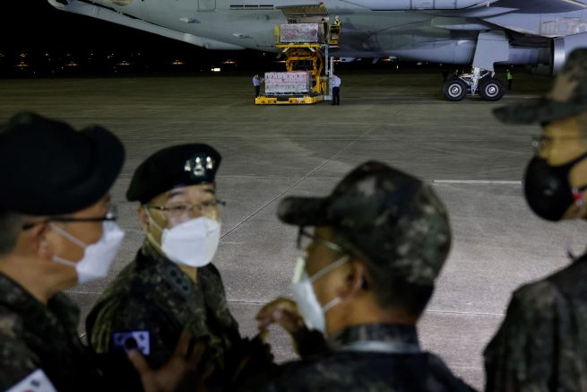 South Korean soldiers talk as a batch of Johnson & Johnsons Janssen Covid-19 vaccines arrive at a military airport in Seongnam, South Korea on June 5, 2021. (Photo by KIM HONG-JI / POOL / AFP) (Photo by KIM HONG-JI/POOL/AFP via Getty Images)
