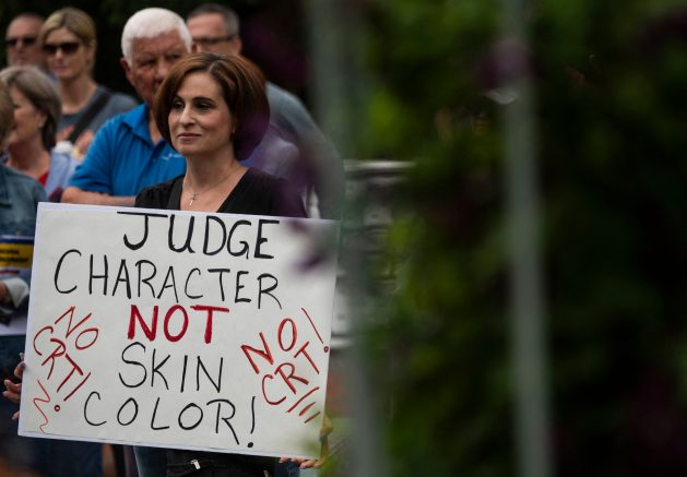 """A woman holds up a sign during a rally against """"critical race theory"""" (CRT) being taught in schools at the Loudoun County Government center in Leesburg, Virginia. (Photo by ANDREW CABALLERO-REYNOLDS/AFP via Getty Images)"""