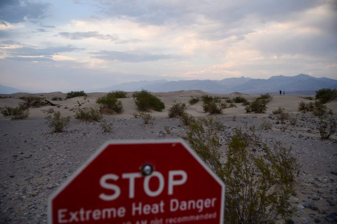 Extreme heat danger signage stands as visitors walk along sand dunes at sunset inside Death Valley National Park in Inyo County, California. (Photo by PATRICK T. FALLON/AFP via Getty Images)