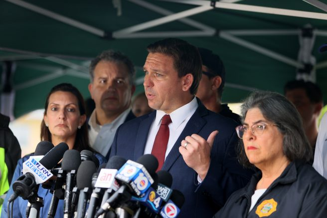 Gov. Ron DeSantis, center, speaks to the media about the 12-story Champlain Towers South condo building that partially collapsed in Surfside, Florida. (Photo by Joe Raedle/Getty Images)