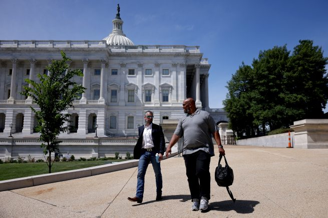 Metropolitan Police Officer Michael Fanone, left, and U.S. Capitol Police Officer Harry Dunn, right, depart from the U.S. Capitol in Washington, DC. (Photo by Anna Moneymaker/Getty Images)