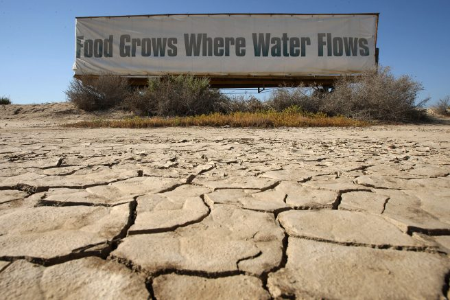 """A sign on a farm trailer reading """"Food grows where water flows,"""" hangs over dry, cracked mud at the edge of a farm near Buttonwillow, California. (Photo by David McNew/Getty Images)"""
