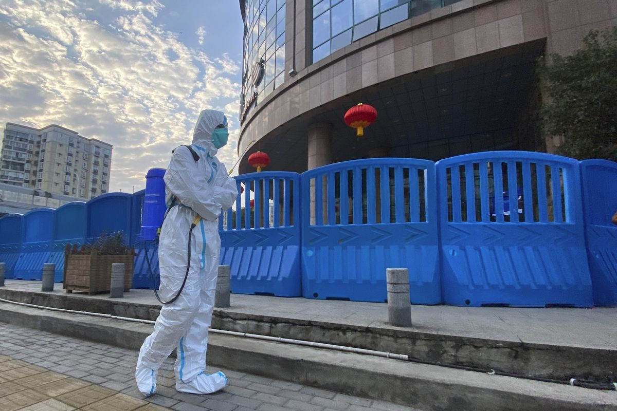 FILE - In this file photo dated Saturday, Feb. 6, 2021, a worker in protectively overalls and carrying disinfecting equipment walks outside the Wuhan Central Hospital where Li Wenliang, the whistleblower doctor who sounded the alarm and was reprimanded by local police for it in the early days of Wuhan's pandemic, worked in Wuhan in central China. (AP Photo/Ng Han Guan, FILE)