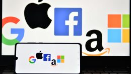 An illustration picture taken in London on December 18, 2020 shows the logos of Google, Apple, Facebook, Amazon and Microsoft displayed on a mobile phone and a laptop screen. - The European Union on December 15 unveiled tough draft rules targeting tech giants like Google, Amazon and Facebook, whose power Brussels sees as a threat to competition and even democracy. (Photo by JUSTIN TALLIS / AFP) (Photo by JUSTIN TALLIS/AFP via Getty Images)