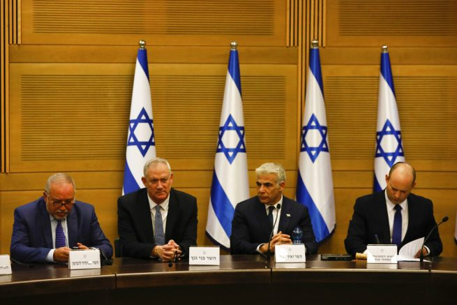 Frome the left, Avigdor Lieberman, Benny Gantz, Yair Lapid and Israel's new prime minister Naftali Bennett hold a first cabinet meeting in Jerusalem Sunday, June 13, 2021. Israel's parliament has voted in favor of a new coalition government, formally ending Prime Minister Benjamin Netanyahu's historic 12-year rule. Naftali Bennett, a former ally of Netanyahu became the new prime minister (AP Photo/Ariel Schalit)
