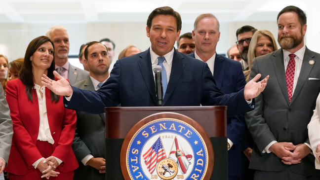 Surrounded by lawmakers, Florida Gov.Ron DeSantis speaks at the end of a legislative session at the Capitol in Tallahassee, Fla. (AP Photo/Wilfredo Lee)