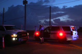 """DAYTONA BEACH, FLORIDA - SEPTEMBER 03: Daytona Beach Shores Police set up a road block to only let residents in as hurricane Dorian looms in the Atlantic Ocean, on September 3, 2019 in Daytona Beach, Florida. Dorian, once expected to make landfall along the Florida coast as a category 4 storm, is currently predicted to turn north and stay off the Florida coast, lessening the impact on the area. Dorian strengthened to a """"catastrophic"""" Category 5 storm, packing winds of 175 mph and bearing down on the northern Bahamas before an expected turn to the north along the eastern seaboard of the United States, according to weather forecasts. (Photo by Mark Wilson/Getty Images)"""