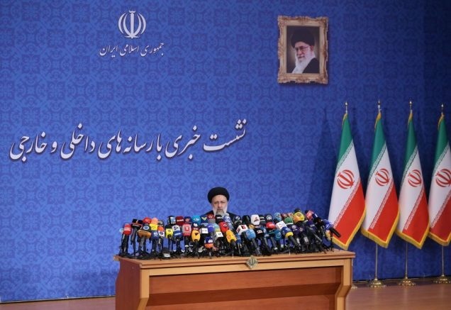 Iran's President-elect Ebrahim Raisi is seated under a protrait of the Islamic republic's supreme leader, Ayatollah Ali Khamenei, during his first press conference since his election on the weekend in Tehran, on June 21, 2021. - Iran's new president hailed what he called a 'massive' voter turnout during last week's presidential election. The ultraconservative cleric was declared the winner of the election on the weekend, replacing moderate Hassan Rouhani. (Photo by ATTA KENARE / AFP) (Photo by ATTA KENARE/AFP via Getty Images)