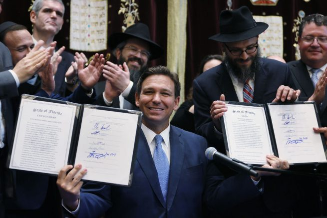 SURFSIDE, FLORIDA - JUNE 14: Florida Gov. Ron DeSantis holds up two bills he signed at the Shul of Bal Harbour on June 14, 2021 in Surfside, Florida. The bills are HB 529 and HB 805. HB 805 ensures that volunteer ambulance services, including Hatzalah, can operate. HB 529 requires Florida schools to hold a daily moment of silence. (Photo by Joe Raedle/Getty Images)