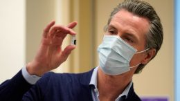 LOS ANGELES, CALIFORNIA - DECEMBER 14: Gov. Gavin Newsom holds up a vial of the Pfizer-BioNTech COVID-19 vaccine at Kaiser Permanente Los Angeles Medical Center on December 14, 2020 in Los Angeles, California. The first doses of the vaccine are being administered to frontline workers in hospitals across the country today. (Photo by Jae C. Hong-Pool/Getty Images)