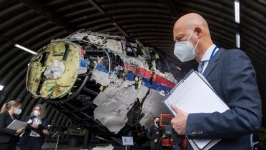 Presiding judge Hendrik Steenhuis, right, and other trial judges and lawyers view the reconstructed wreckage of Malaysia Airlines Flight MH17, at the Gilze-Rijen military airbase, southern Netherlands, Wednesday, May 26, 2021. (AP Photo/Peter Dejong, Pool)
