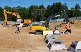Environmental activists set up their tents near construction equipment to disrupt the Line 3 pipeline pumping station near the Itasca State Park, Minnesota on June 7, 2021. - Line 3 is an oil sands pipeline which runs from Hardisty, Alberta, Canada to Superior, Wisconsin in the United States. In 2014, a new route for the Line 3 pipeline was proposed to allow an increased volume of oil to be transported daily. While that project has been approved in Canada, Wisconsin, and North Dakota, it has sparked continued resistance from climate justice groups and Native American communities in Minnesota. While many people are concerned about potential oil spills along Line 3, some Native American communities in Minnesota have opposed the project on the basis of treaty rights and calling President Biden to revoke the permits and halt construction. (Photo by Kerem YUCEL / AFP) (Photo by KEREM YUCEL/AFP via Getty Images)