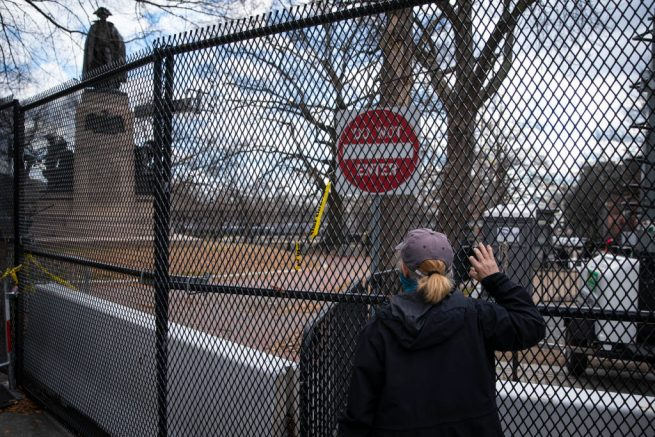 WASHINGTON, DC - JANUARY 17: A woman holds onto a fence surrounding Lafayette Park as part of the expanded protective perimeter around the White House on January 17, 2021 in Washington, DC. As a result of last week's riot at the U.S. Capitol, increased security measures have been put in place, including 25,000 National Guard soldiers, ahead of the inauguration of Joe Biden as the 46th U.S. President. (Photo by Sarah Silbiger/Getty Images)
