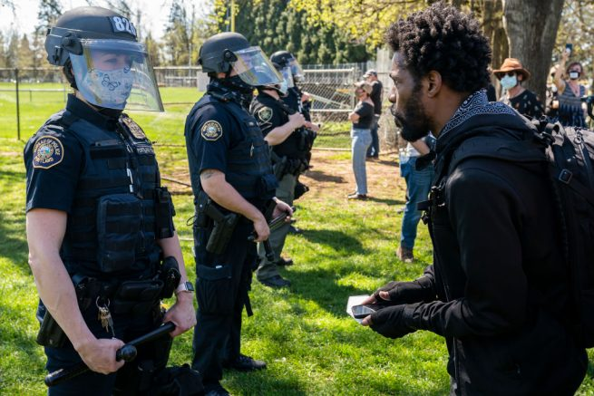 PORTLAND, OR - APRIL 16: A protester argues with a Portland riot officer following the police shooting of a homeless man in Lents Park on April 16, 2021 in Portland, Oregon. The shooting comes amid heightened tensions between police and activists as the country awaits a verdict in the trial of Derek Chauvin. (Photo by Nathan Howard/Getty Images)