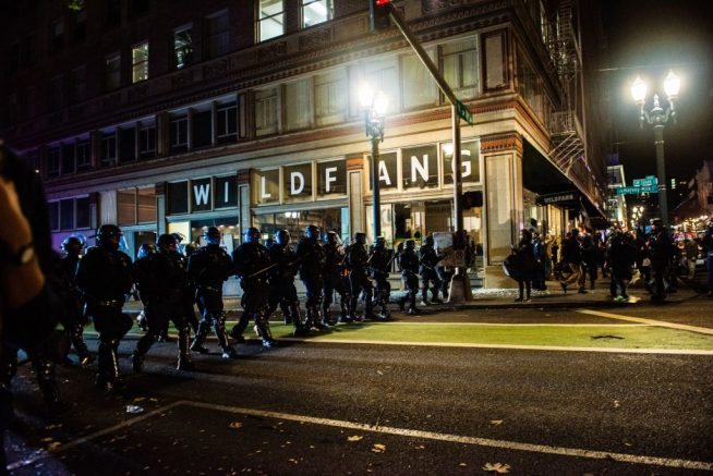 """Riot police march as they try to disperse protesters in Portland, Oregon on November 4, 2020, during a demonstration called by the """"Black Lives Matter"""" movement, a day after the US Presidential Election. - Democratic presidential challenger Joe Biden on November 4 neared the magic number of 270 electoral votes needed to win the White House with several battleground states still in play, as incumbent President Donald Trump challenged the vote count. (Photo by Kathryn ELSESSER / AFP) (Photo by KATHRYN ELSESSER/AFP via Getty Images)"""