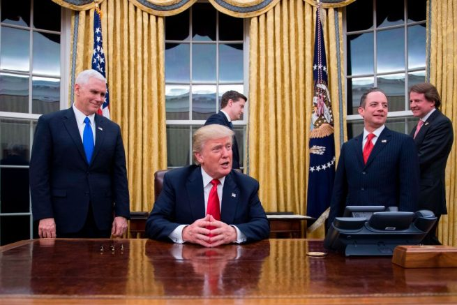 """(FILES) US President Donald Trump (C) speaks to the press as he waits at his desk before signing conformations for General James Mattis as US Secretary of Defense and General John Kelly as US Secretary of Homeland Security, as Vice President Mike Pence (L) and White House Chief of Staff Reince Priebus (R) look on, in the Oval Office of the White House in Washington, DC, January 20, 2017. While the new US president has shown a capacity to change, both his tone and his positions, he has been unable to show the world a """"new"""" Trump, with a steady presidential style and a clearly articulated worldview. As the symbolic milestone of his 100th day in power, which falls on April 29, 2017, draws near, a cold, hard reality is setting in for the billionaire businessman who promised Americans he would """"win, win, win"""" for them. At this stage of his presidency, he is the least popular US leader in modern history (even if his core supporters are still totally behind him.) / AFP PHOTO / JIM WATSON / TO GO WITH AFP STORY, US-politics-Trump-100days (Photo credit should read JIM WATSON/AFP via Getty Images)"""