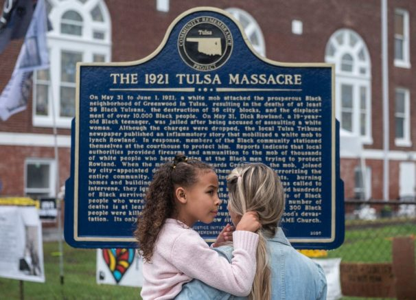 A mother holds her daughter as she reads a sign, before the arrival of US President Joe Biden, in the Greenwood district on the 100th anniversary of the 1921 Tulsa Massacre in Tulsa, Oklahoma on June 1, 2021. - In Tulsa, the city that still bears the scars of a 1921 racial massacre, African American residents are eagerly awaiting the arrival of President Joe Biden on Tuesday, hoping he will hear their call for financial reparations. (Photo by ANDREW CABALLERO-REYNOLDS / AFP) (Photo by ANDREW CABALLERO-REYNOLDS/AFP via Getty Images)