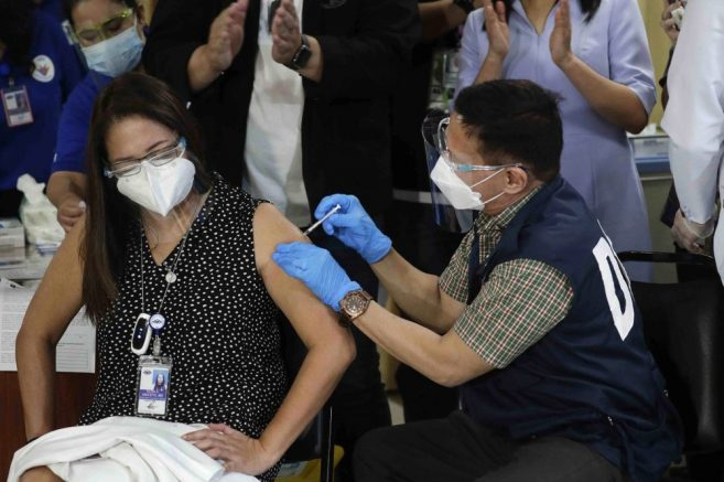 Health Secretary Francisco Duque III, right, injects China's Sinovac vaccine on Filipino doctor Eileen Aniceto during the first batch of vaccination at the Lung Center of the Philippines in Quezon city, Philippines. (AP Photo/Aaron Favila)