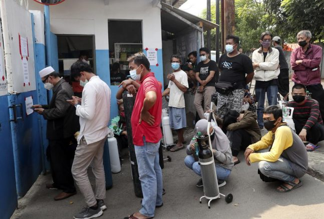 People wait for their turn to refill their oxygen tanks at a recharging station in Jakarta, Indonesia. The Southeast Asia country is running out of oxygen as it endures a devastating wave of coronavirus cases. (AP Photo/Tatan Syuflana)