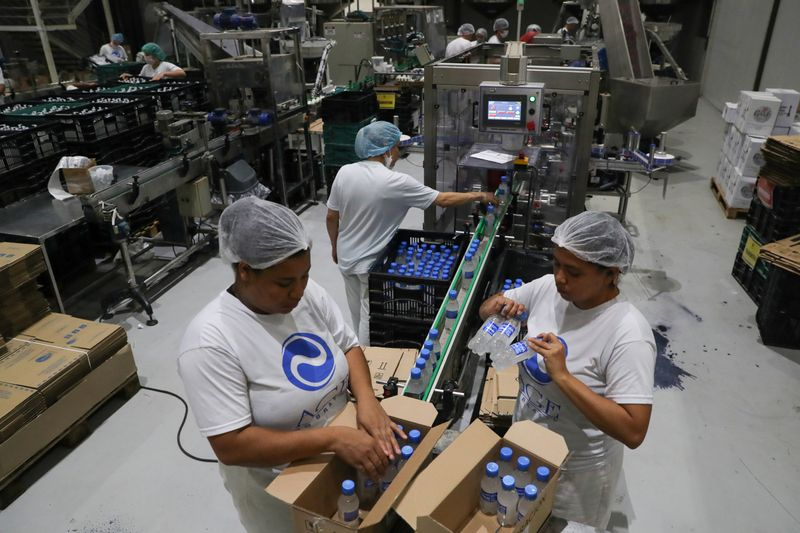 Employees fill boxes with ethanol-based hand sanitizers in AGE do Brasil factory, hired by brewing Ambev to produce hand sanitizers to donate to public hospitals during the coronavirus disease (COVID-19) outbreak in Vinhedo