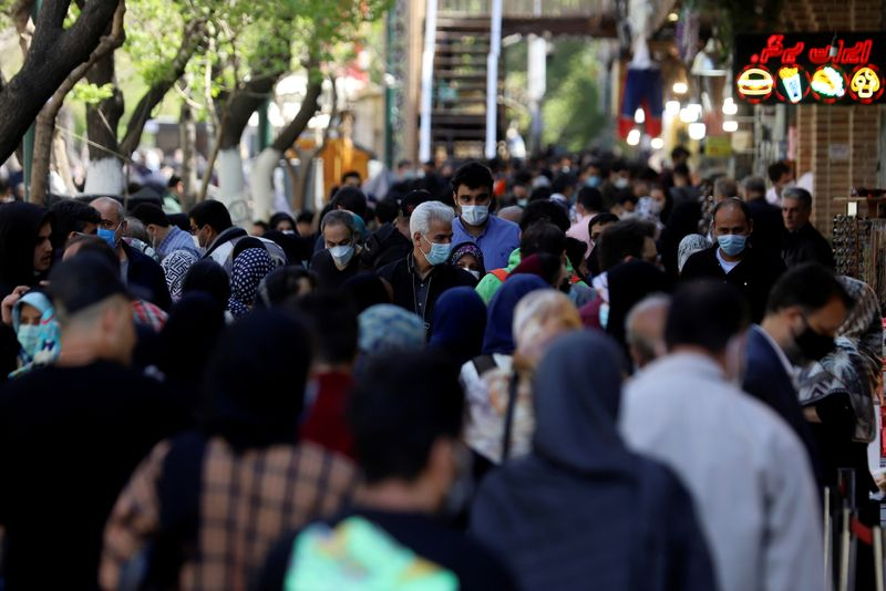 FILE PHOTO: Iranians wearing protective face masks against the coronavirus walk in a crowded area of the capital Tehran, Iran