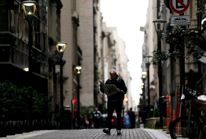 FILE PHOTO: A man reads a newspaper as he walks in Buenos Aires' financial district