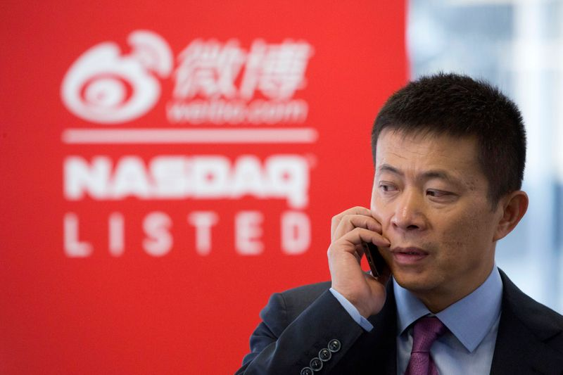 Weibo Corporation Chairman Charles Chao talks on a cell phone before the opening of trading for Weibo at the NASDAQ MarketSite in Times Square on day one of its initial public offering (IPO) on The NASDAQ Stock Market in New York