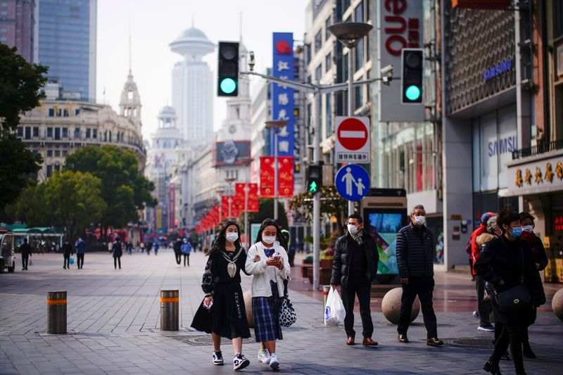 FILE PHOTO: FILE PHOTO: People wearing face masks walk at a main shopping area in Shanghai