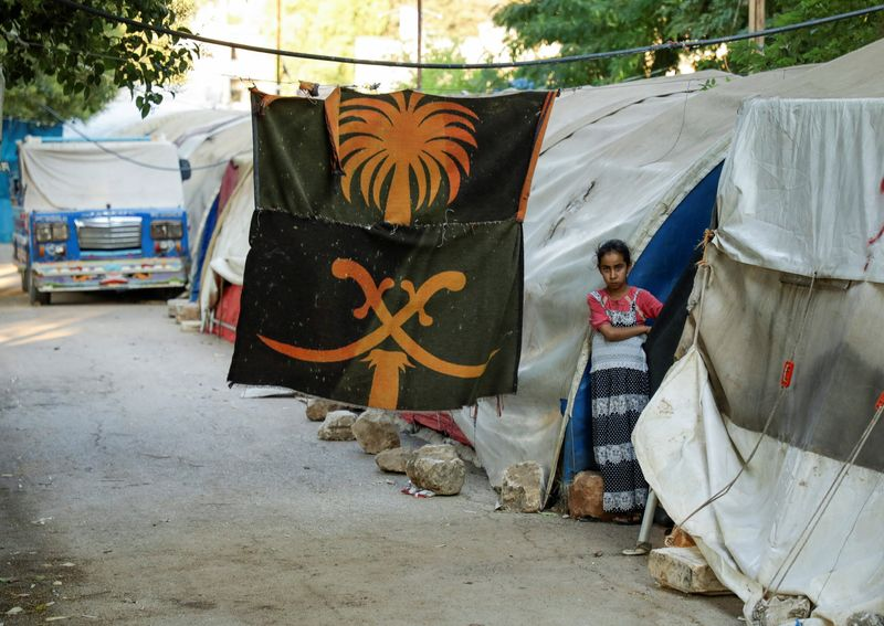 A girl stands outside a tent at a camp for internally displaced people in the opposition-held Idlib
