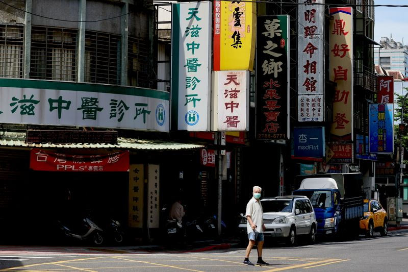 A man crosses the street while wearing a protective mask following the recent rise in coronavirus disease
