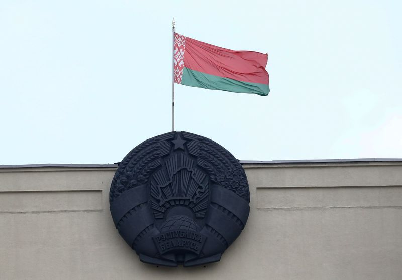 Belarusian state flag and emblem are seen on a building at Independence Square in Minsk