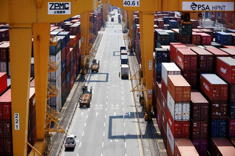 A truck driver stands next to his truck as he gets ready to transport a shipping container at Pusan Newport Terminal in Busan