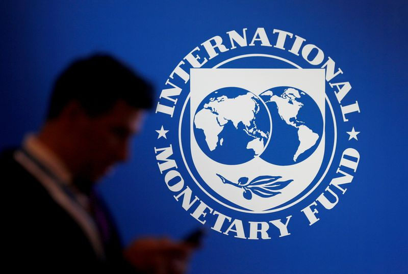 FILE PHOTO: A participant stands near a logo of IMF at the International Monetary Fund - World Bank Annual Meeting 2018 in Nusa Dua
