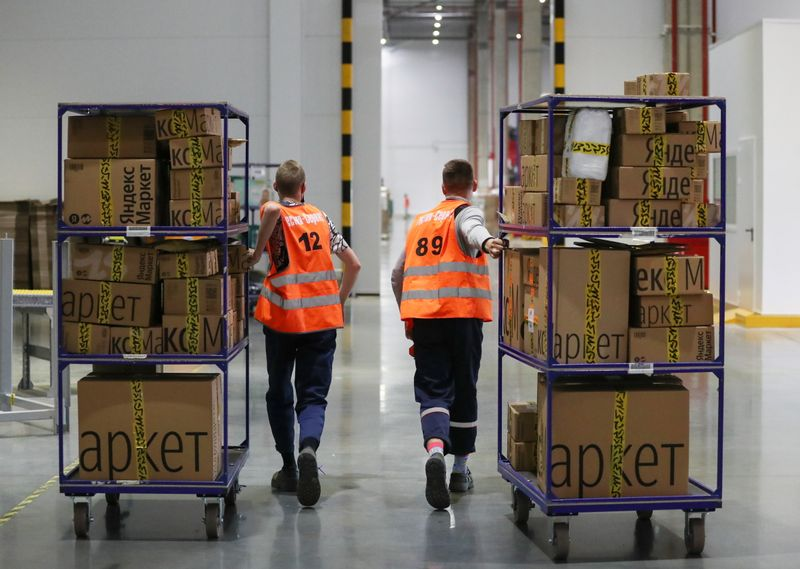 Employees move boxes at a logistics centre of the Yandex.Market e-commerce platform in Moscow