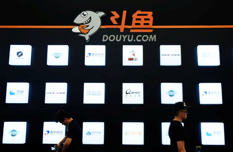 People walk past a booth of live-streaming platform Douyu at the ChinaJoy digital entertainment expo in Shanghai