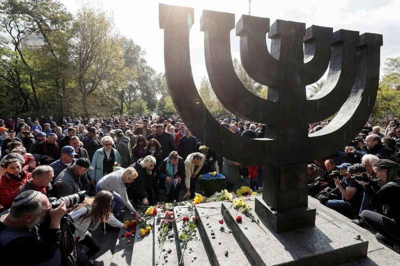 FILE PHOTO: People place flowers during a ceremony at a monument commemorating the victims of Babyn Yar in Kiev