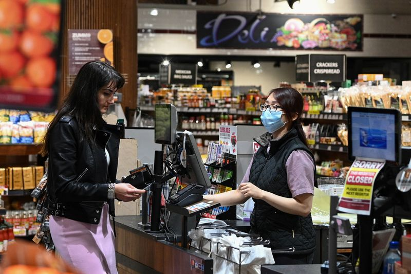 An employee wears a protective face mask while ringing up a customer at a specialty grocery store in Sydney