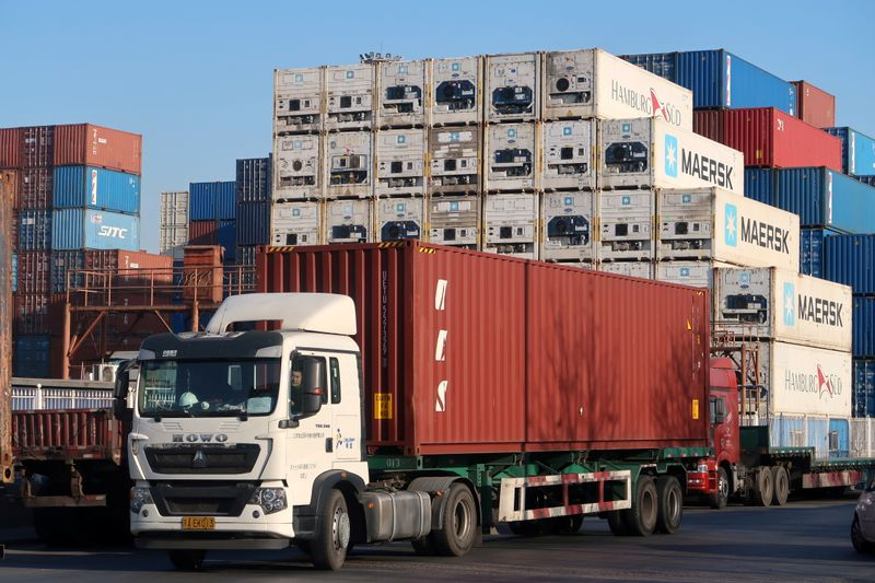Worker drives a truck carrying a container at a logistics center near Tianjin port