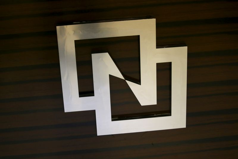 FILE PHOTO: The logo of Tsinghua Unigroup is seen in its office in Beijing