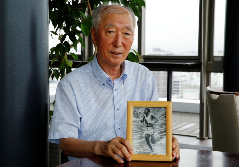 Son Chung-in poses with a photograph of his father, Sohn Kee-chung, who won the 1936 Berlin Olympics marathon event, during an interview with Reuters in Yokohama