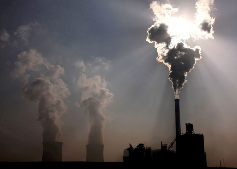 FILE PHOTO: A coal-burning power plant can be seen behind a factory in China's Inner Mongolia Autonomous Region