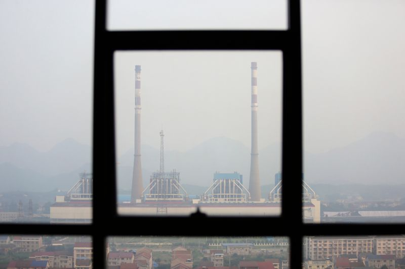 Chimneys are seen through a window at a coal-fired power plant on a hazy day in Shimen county