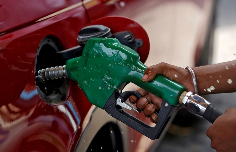 FILE PHOTO: A worker holds a nozzle to pump petrol into a vehicle at a fuel station in Mumbai