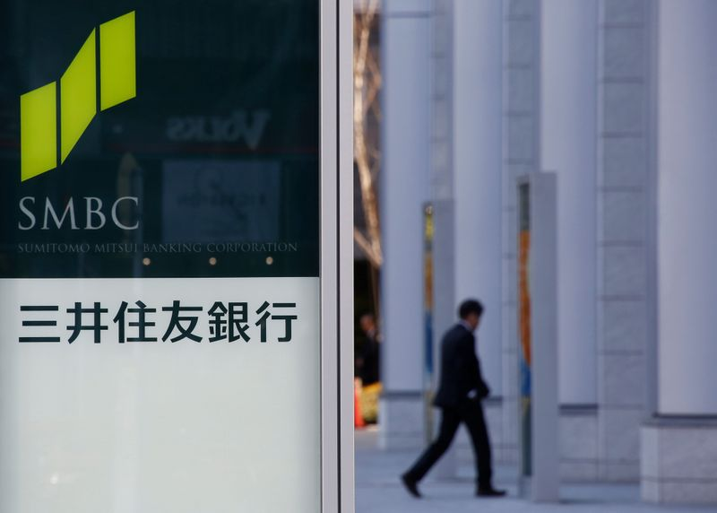 Workers clean windows next to a signboard of Sumitomo Mitsui Financial Group' SMBC Friend Securities in Tokyo