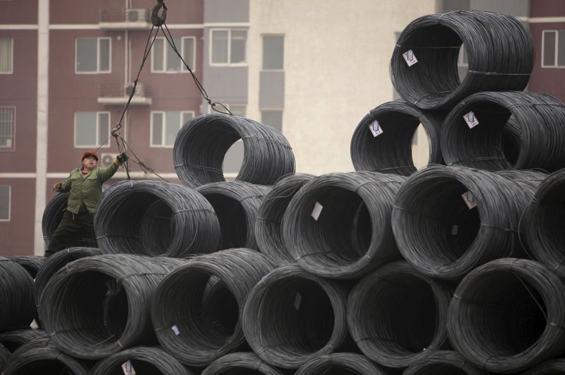 A labourer works on coils of steel wire at a steel wholesale market in Beijing