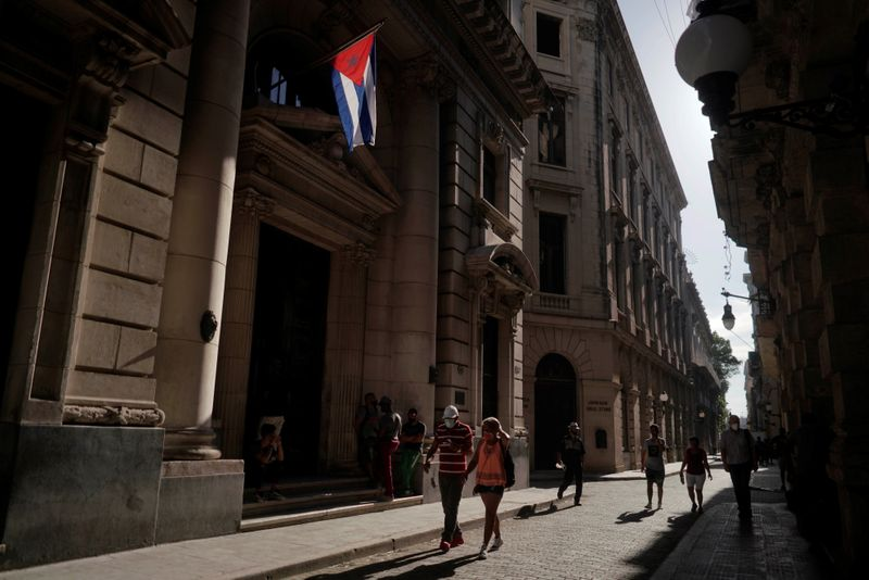 FILE PHOTO: People pass under a Cuban flag in Havana
