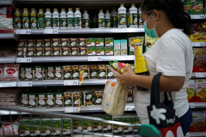 A woman shops coconut products at a supermarket in Bangkok