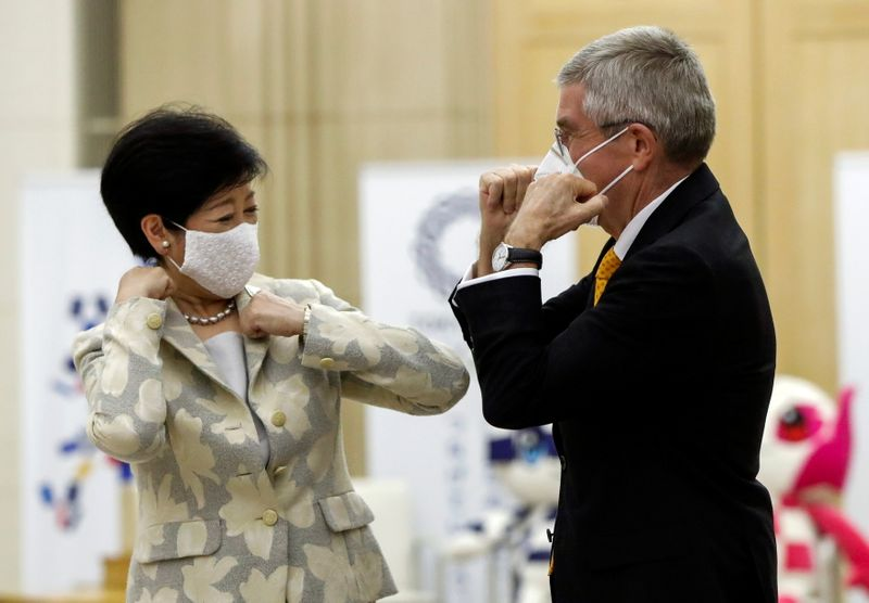 Tokyo Governor Yuriko Koike and Thomas Bach, President of the International Olympic Committee (IOC), bump elbows at the start of their talks at Tokyo Metropolitan Government Office Building in Tokyo